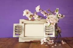 Vintage blank photo frame next to spring flowers Stock Photos