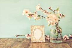 Vintage blank photo frame next to spring flowers Royalty Free Stock Photos