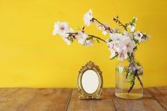 Vintage blank photo frame next to spring white flowers on wooden table. Stock Photos