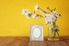 Vintage blank photo frame next to spring white flowers on wooden table. Stock Images