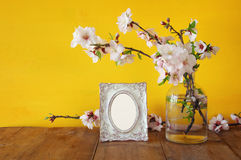 Vintage blank photo frame next to spring white flowers Stock Photography