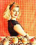 Vintage blond housewife and cupcakes. Vintage image with the blond housewife and cupcakes on the orange background Royalty Free Stock Image
