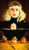 Vintage blond housewife and cupcakes with knives Stock Image
