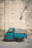 Vintage blu car near a medieval wall Royalty Free Stock Images