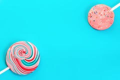 Vintage Blue Background With Two Candy. Two round striped spotted colored pink and blue candy on a turquoise background. Vintage background with space for copy Stock Photo