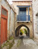 Vintage blue balcony above the arch in stone house, Lefkara village Cyprus. Old street with stone buildings n famous Cyprus see sights village Lefkara. Blue Stock Photo