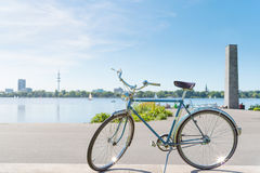 Vintage blue bicycle parked at lakeshore of Alster Lake in Hamburg Stock Image