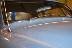 VINTAGE BLUE CAR WITH VIEW OF WINDSHIELD AND HOOD. A view of the hood and windshield of a vintage 1950`s blue car with the antenna and mirror and windshield stock photos