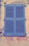 Vintage blue close window with shutters. In old stone house, Provence, France. Toned image Royalty Free Stock Image