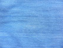 Vintage blue color faded jeans fabric textured background.  stock photos