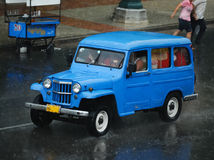Vintage Blue Cuban Taxi Car. Overcrowded blue old style taxi cab for Cuban residents at the street road in Havana during tropical thunderstorm stock photography