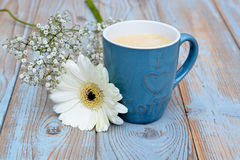 Vintage blue cup of coffee on a wooden background with white Gerbera daisy decoration Royalty Free Stock Photography