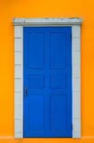 Vintage blue door in bright yellow wall Royalty Free Stock Photo