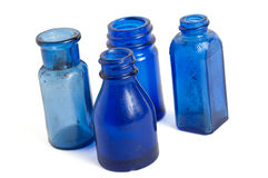 Vintage blue glass bottles. Collection of four vintage blue glass bottles isolated on white royalty free stock photo