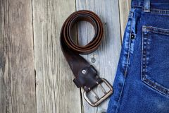 Vintage blue jeans and old leather belt on boards. still life in a nostalgic manner. Vintage blue jeans and old leather belt on aged boards. still life in a royalty free stock images