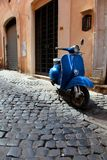 Vintage blue motor scooter in Rome. Vintage blue motor scooter parked in a Roman cobblestone alley Stock Photography