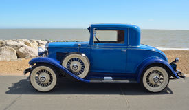 Vintage  Blue Motorcar with white wall tyres parked on seafront promenade. Stock Image