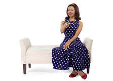 Vintage Blue Poka Dot Dress. Woman wearing a blue ploka dot dress on a traditional chaise furniture.  The model is isolated on a white background Royalty Free Stock Image