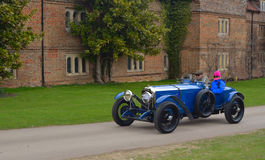 Vintage blue racing car being driven past  front of old building. Royalty Free Stock Images