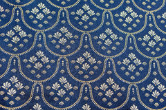 Vintage blue silver bed spread. Close up of traditional Sicilian bed spread made from blue fabric with silver stitched pattern of fleurs de lys from Sicily Royalty Free Stock Images