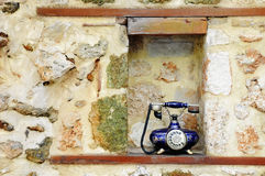 Vintage blue telephone. Vintage blue dial up telephone in a rectangular recess created in an internal  pointed stone wall with wooden base built into it Royalty Free Stock Photo