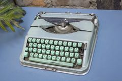 Vintage blue typewriter with turquoise green buttons stands on a table with a branch of a plant stock photo