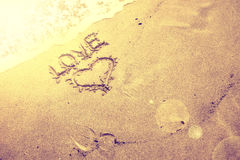 Vintage blurred sunny love handwriting. Vintage blurred sunny golden love and heart handwriting sign on sea sand with wave. Gold color filter effect used Stock Photos