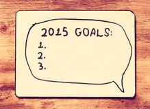 Vintage board with phrase 2015 goals over wooden table. retro vintage filter Royalty Free Stock Photos