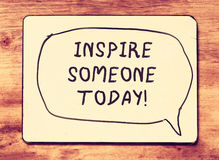 Vintage board with the phrase inspire someone today! written on it. retro filtered image.  Stock Image