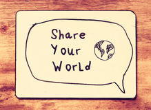 Vintage board with the phrase share your world written on it. retro filtered image.  Royalty Free Stock Image