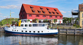 Vintage boat docked at Dane rivers quay. Old Town district. Klaipeda, Lithuania. Royalty Free Stock Photography