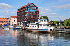 Vintage boat docked at Dane rivers quay. Old Town district. Klaipeda, Lithuania. Royalty Free Stock Photo