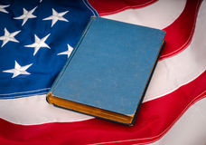 .Vintage book on American flag royalty free stock image
