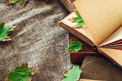 Vintage book with autumn maple leaves on the table the laid sack Stock Images