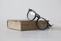 Vintage book with black reading glasses on top. Vintage book on white wooden background with black reading glasses on top stock photo