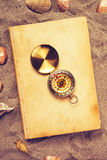Vintage book and compass on sandy beach Royalty Free Stock Photos