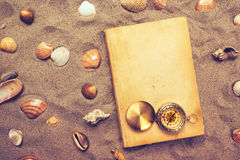 Vintage book and compass on sandy beach Royalty Free Stock Images