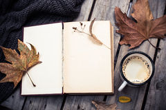 Vintage book, knitted sweater with autumn leaves and coffee mug Royalty Free Stock Image