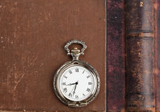 Vintage book with leather backs. Ancient book with pocket watch royalty free stock photo