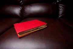 Vintage book on a leather sofa. Close up of a vintage book on a brown leather sofa Royalty Free Stock Photography