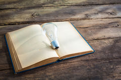 Vintage book and light bulb on wood table Royalty Free Stock Photos