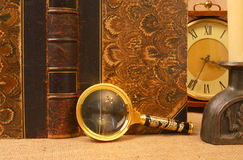 Vintage book, magnifying glass, clocks and candlestick Stock Photo