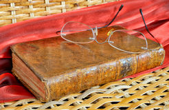 Vintage book and old frameless glasses Royalty Free Stock Photography