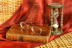 Vintage book and old frameless glasses Stock Images