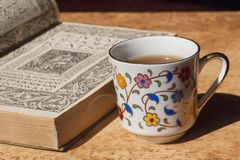 Vintage book printed at 18th century on table with old fashion designed cup of coffee. Selective focus Royalty Free Stock Photo