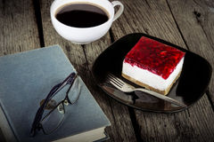 Vintage book reading cup of coffee and cheese cake on grungy wood. En background Royalty Free Stock Photos