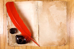 Vintage book, red feather pen, inkwell Stock Images