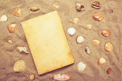 Vintage book and sea shells on sandy beach Royalty Free Stock Images