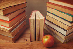 Vintage books with apple on wooden table. Reading a lot of books concept Stock Photography