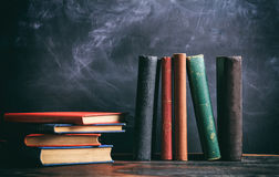 Vintage books on blackboard background royalty free stock photography